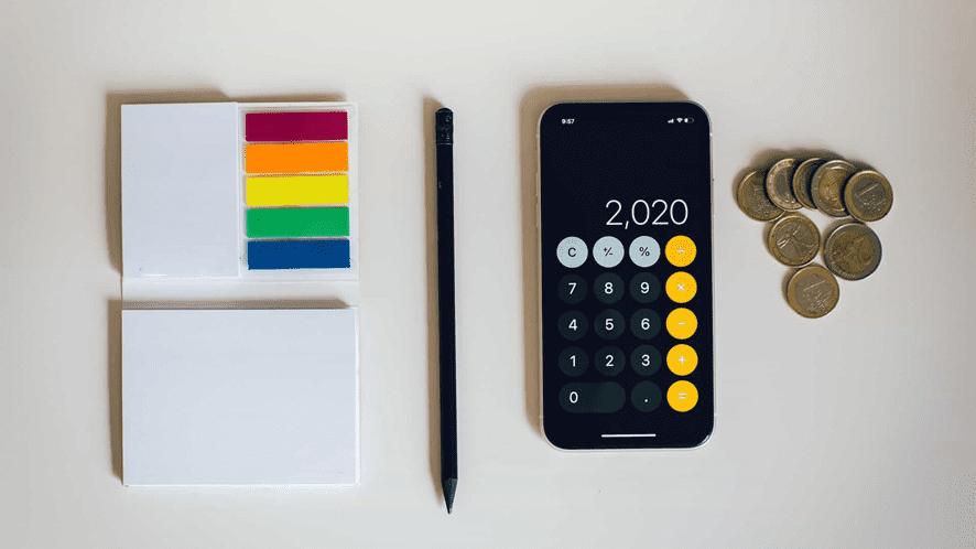 Calculadora y libro al lado con monedas